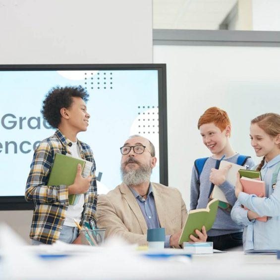 group-of-kids-talking-to-teacher-in-school.jpg